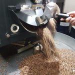 Kaffeebohnen werden in Röster geschüttet